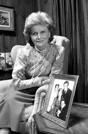 "FILE - In this Sept. 22, 1986 file photo, actress Barbara Billingsley poses next to a portrait of her television family, Hugh Beaumont, Tony Dow, Jerry Mathers and herself as the Cleaver family from ""Leave It To Beaver."" Why settle for one great mom when, as any TV viewer knows, you can adopt a series of them? AP Television Writer Lynn Elber chooses five of the best sit com moms, from the demure 1950s version, such as the role of June Cleaver played by Barbara Billingsley, to the freewheeling 21st-century incarnation. (AP Photo/Doug C. Pizac, File)"