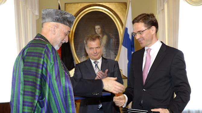 Afghan President Hamid Karzai, left, shakes hands with  Finnish Prime Minister Jyrki Katainen with Finnish President Sauli Niinisto  in the background, during a press conference,  in Helsinki, Finland, Monday, April 29, 2013. Afghan President Karzai is in Finland on a working visit.  On the agenda are discussions of Finnish Afghan relations and Afghanistan's development. (AP Photo/Lehtikuva,  Heikki Saukkomaa)  FINLAND OUT. NO THIRD PARTY SALES.