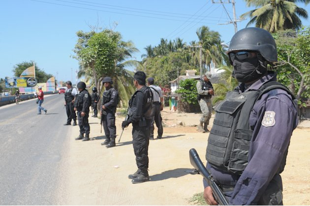 State police stand at a roadblock due to stepped up security after masked armed men broke into a beach home, raping six Spanish tourists who had rented the house in Acapulco, Mexico, Tuesday Feb. 5, 2