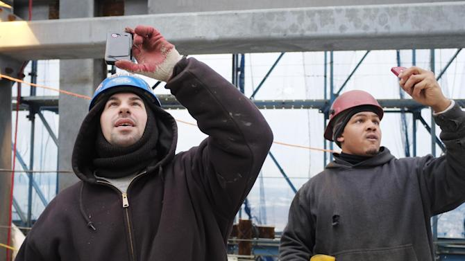 Construction workers take photographs as the first piece of the spire for One World Trade Center is lowered by construction cranes into position on the roof of the tower, Tuesday, Jan. 15, 2013 in New York. When the spire is completed the building will top off at 1776 feet (541 meters), making it the tallest building in North America. (AP Photo/Mark Lennihan)
