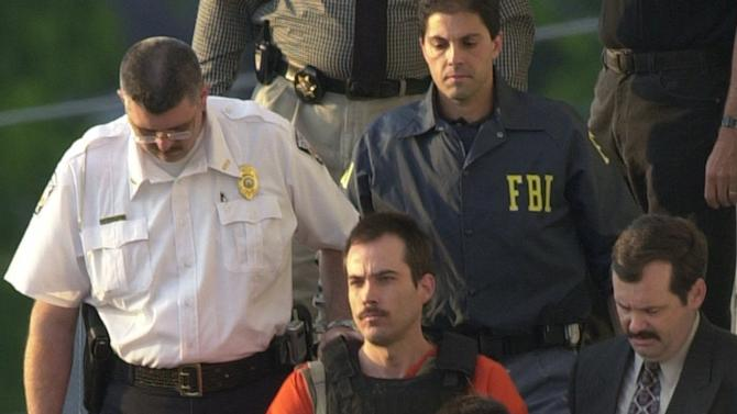 FILE - In this June 2, 2003 file photo, Eric Robert Rudolph, center, is escorted from the sheriff's department in Murphy, N.C. Rudolph has published his autobiography from prison with the help of his brother.  Eric Rudolph pleaded guilty to setting off a bomb during the 1996 Olympics in Atlanta, and he also admitted to bombing a Birmingham abortion clinic in 1998. Two people died in the blasts. A prosecutor says authorities will look into seizing any money Rudolph might make from the book. The work explains his motive for the bombings and recounts his capture after more than five years on the run (AP Photo/Mary Ann Chastain)
