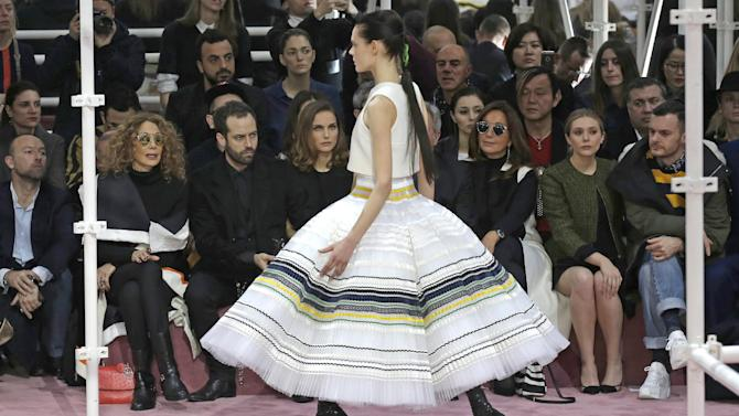 A model wears a creation as Marisa Berenson, second left, Benjamin Millepied, third left, his wife actress Natalie Portman, fourht left, look on during Christian Dior's Spring-Summer 2015 Haute Couture fashion collection presented in Paris, France, Monday, Jan. 26, 2015. (AP Photo/Francois Mori)