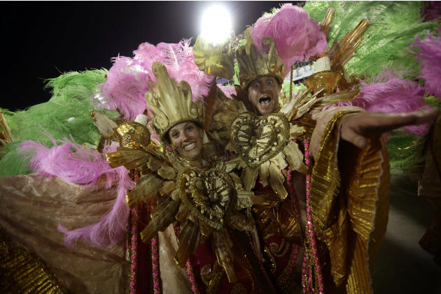 U.S. citizen Paul Leaury, right, and an unidentified fellow foreign member of the Mangueira samba school, dance during a carnival parade at the Sambadrome in Rio de Janeiro, Brazil, Tuesday, Feb. 12,