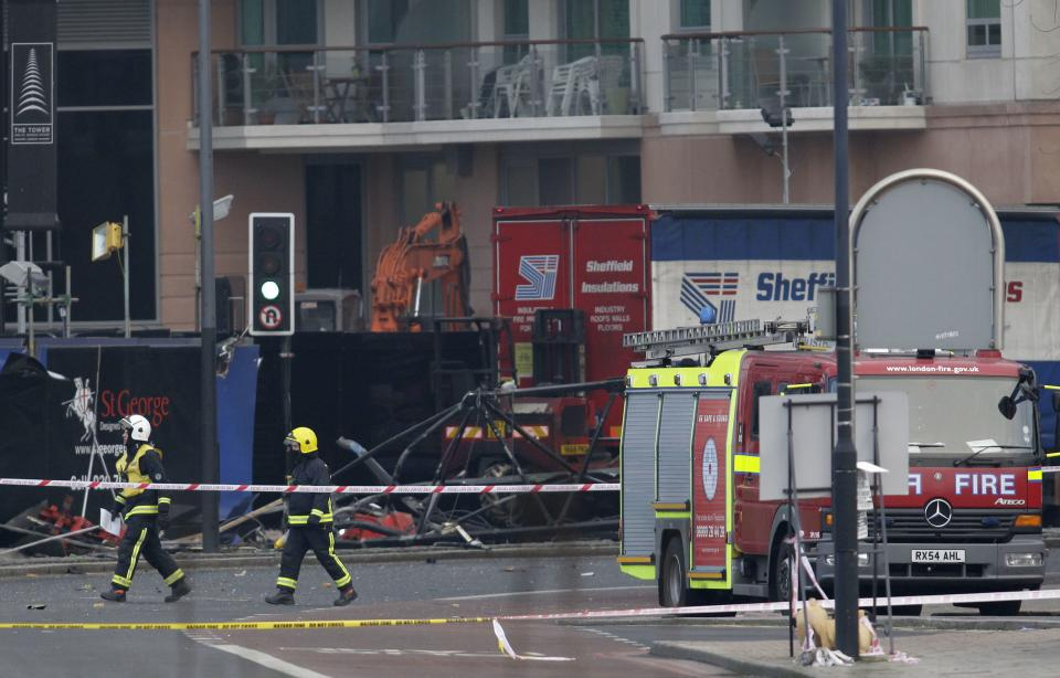 Firefighters walk pass the section of damaged crane on the ground after a helicopter crashed into the crane on top of a building in central London, Wednesday Jan. 16, 2013. Police say two people were killed when a helicopter crashed Wednesday during rush hour in central London after apparently hitting a construction crane on top of a building. (AP Photo/Sang Tan)