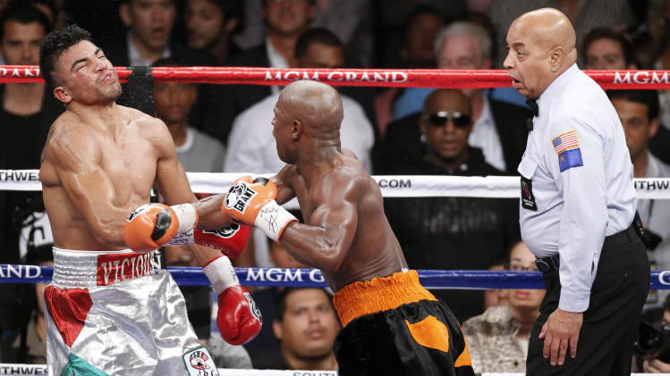 Floyd Mayweather, center, delivers a knockout punch to Victor Ortiz as referee Joe Cortez, right, looks on in the fourth round during a WBC welterweight title fight, Saturday, Sept. 17, 2011, in Las Vegas. (AP Photo/Eric Jamison)