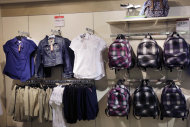 In this photo of July 31, 2013, school uniforms by Arizona are displayed at JC Penney in New York. The government reports how much U.S. businesses adjusted their stockpiles in July on Friday, Sept. 13, 2013. (AP Photo/Mark Lennihan)