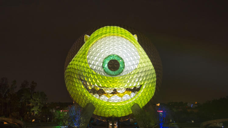 "In this Thursday, April 25, 2013 photo provided by Disney, the image of Mike Wazowski, a character from the upcoming Disney-Pixar animated film ""Monsters University,"" is projected on the exterior of the Spaceship Earth attraction at Epcot in Lake Buena Vista, Fla. The 180-foot-tall light projection marked Disney Parks' announcement of its ""Monstrous Summer"" events for 2013.  (AP Photo/Disney, David Roark)"