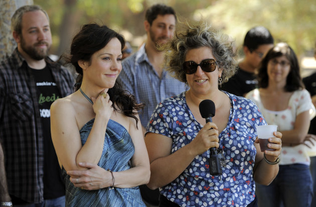 "Mary-Louise Parker, left, star of the Showtime series ""Weeds,"" looks on as the show's creator and executive producer Jenji Kohan addresses cast and crew members at a party to celebrate the show's 100th episode, Tuesday July 17, 2012, in Los Angeles. ""Weeds"" is in its final season and will end its eight-year run in September. (Photo by Chris Pizzello/Invision/AP)"