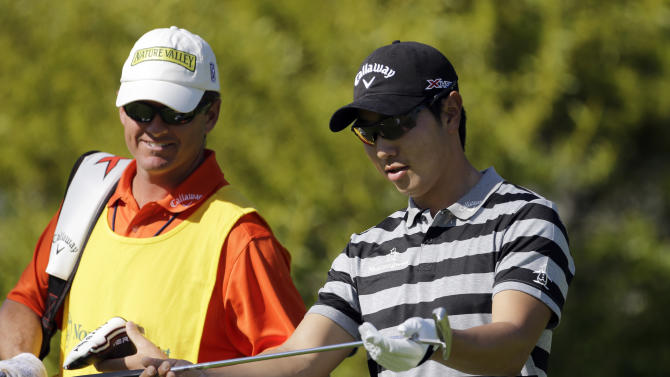 ADDS NAME OF CADDIE - Sang-Moon Bae, of South Korea, looks at his club on the sixth hole in the second round of the Northern Trust Open golf tournament at Riviera Country Club in the Pacific Palisades area of Los Angeles Friday, Feb. 15, 2013. At left is his caddie, Matt Minister. (AP Photo/Reed Saxon)