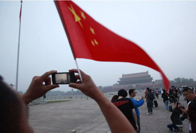 Visitors take photos near a Chinese national flag with Tiananmen Gate in the background as many gathered to mark the anniversary of the deadly 1989 crackdown on pro-democracy protestors which centered