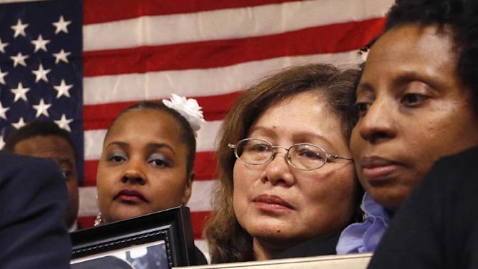 Women who have lost family members to gun violence stand behind Robin Kelly, left, as she celebrates her special Democratic primary election win for Illinois' 2nd Congressional District, once held by Jesse Jackson Jr., Tuesday, Feb. 26, 2013, in Matteson, Ill. In this campaign, New York Mayor Michael Bloomberg's super PAC had a simple formula: choose a strong anti-gun candidate, blast rivals with any hint of support from the National Rifle Association and add in $2.2 million in resources. It worked. Bloomberg's candidate Kelly won. (AP Photo/Charles Rex Arbogast)