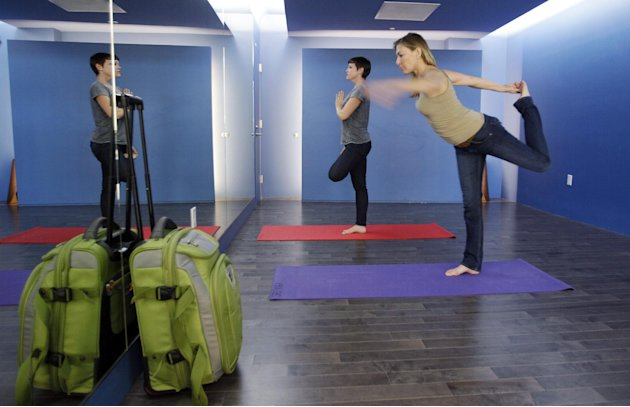In this Friday, Jan. 27, 2012 photo, travelers Maria Poole, right, and Lindsey Shepard, practice yoga at San Francisco International Airport's new Yoga Room, in San Francisco. The quiet, dimly lit stu