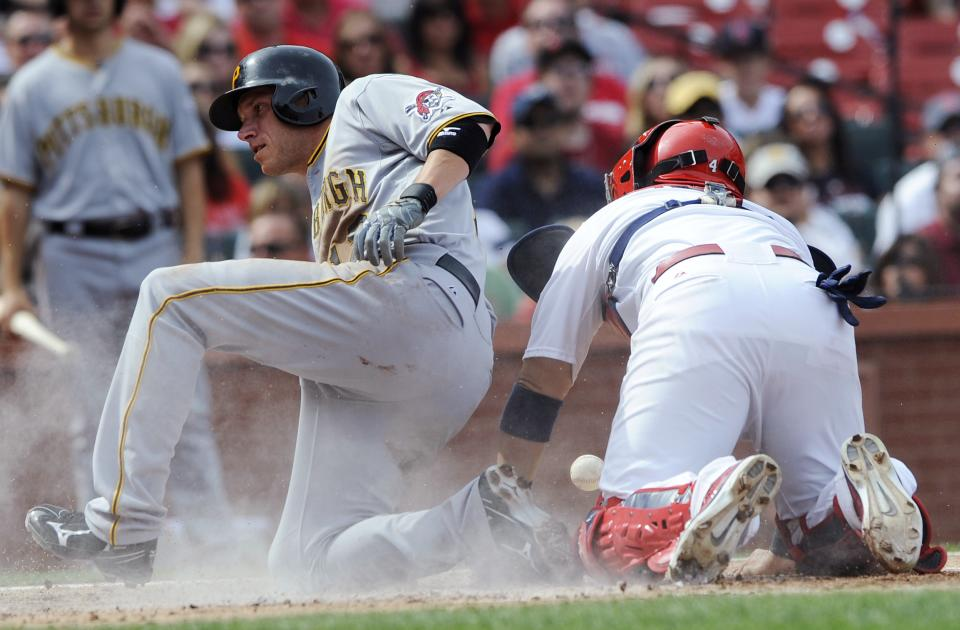 Pittsburgh Pirates' Clint Barmes, left, scores on a hit by Jordy Mercer as St. Louis Cardinals catcher Yadier Molina can't make the tag in the third inning of a baseball game Saturday, August 18, 2012, in St. Louis. (AP Photo/Bill Boyce)
