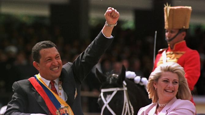 FILE - In this Feb. 4, 1999 file photo, Venezuela's newly sworn in President Hugo Chavez salutes the crowd next to his wife Marisabel Chavez during a military parade commemorating the seventh anniversary of his failed 1992 coup in Caracas, Venezuela.  Venezuela's Vice President Nicolas Maduro announced on Tuesday, March 5, 2013 that Chavez has died.  Chavez, 58, was first diagnosed with cancer in June 2011.  (AP Photo/Douglas Engle, File)