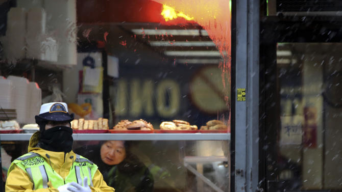 A crossing guard takes cover from the snow under the awning of a restaurant in New York's Chinatown, Friday, Feb. 8, 2013. A storm poised to dump up to 3-feet of snow from New York City to Boston and beyond beginning Friday could be one for the record books, forecasters warned, as residents scurried to stock up on food and water and road crews readied salt and sand. (AP Photo/Mary Altaffer)