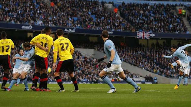 Manchester City's Carlos Tevez (R) shoots to score his side's first goal during their FA Cup match against Watford at The Etihad Stadium