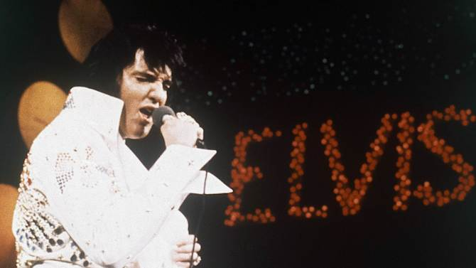 """FILE - This 1972 file photo shows Elvis Presley, the King of Rock """"n"""" Roll, during a performance. The former Beverly Hills home of the late Elvis Presley and his wife Priscilla is up for sale for a cool $12.9 million. Real estate website operator Trulia says the home hit the market Wednesday, Oct. 10, 2012. (AP Photo, file)"""