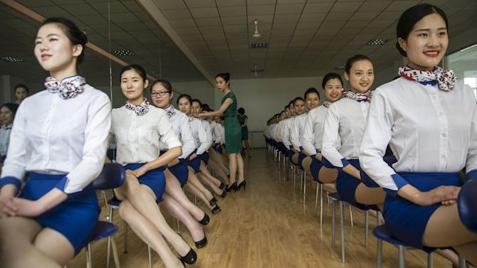 An instructor adjusts the posture of students of flight attendant major during a training session at Anhui Foreign Languages University, in Hefei