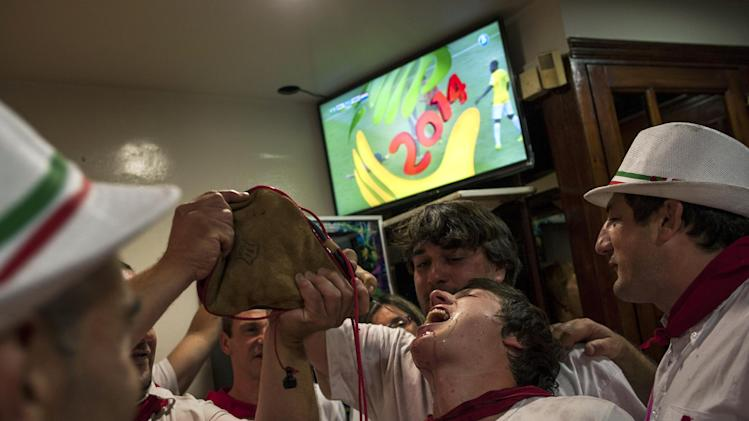 Reveler drinks from wineskin as a TV shows the World Cup soccer match between Brazil and the Netherland at a bar during the San Fermin festival, in Pamplona, Spain, Saturday, July 12, 2014. Revelers from around the world arrive to Pamplona every year to take part in some of the eight days of the running of the bulls. (AP Photo/Alvaro Barrientos)