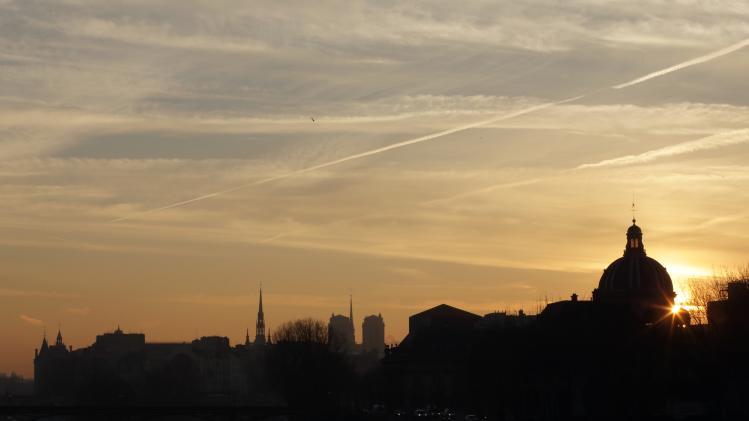 Clouds fill the sky as the sun rises over the Seine River in the early morning in Paris