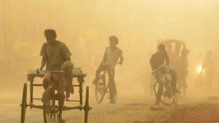 Indians try to keep their balance as they ride past a dust storm in Agartala, in the northeastern Indian state of Tripura, Saturday, April 19, 2014. (AP Photo/Ramakanta Dey)