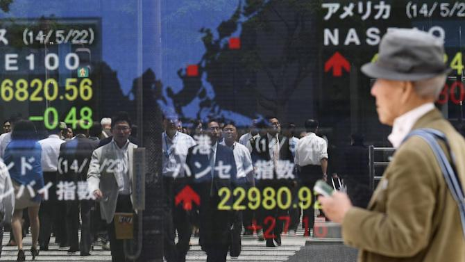 A passer-by looks at an electronic stock board of a securities firm in Tokyo, Friday, May 23, 2014. Japan's Nikkei 225 was up 0.9 percent at 14,473.19 after the dollar climbed to near 102 yen overnight. A weaker yen is a plus for Japan's powerhouse export manufacturers. (AP Photo/Koji Sasahara)