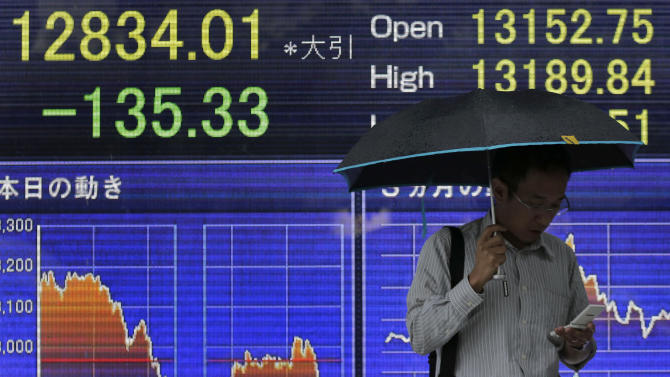 A man checks his mobile phone in front of the electronic stock board of a securities firm in Tokyo, Wednesday, June 26, 2013. Global stock markets staged a modest recovery Wednesday, boosted by strong data releases that portray a U.S. economy on the upswing. Japan's Nikkei 225 fell 1 percent to close at 12,834.01. (AP Photo/Itsuo Inouye)