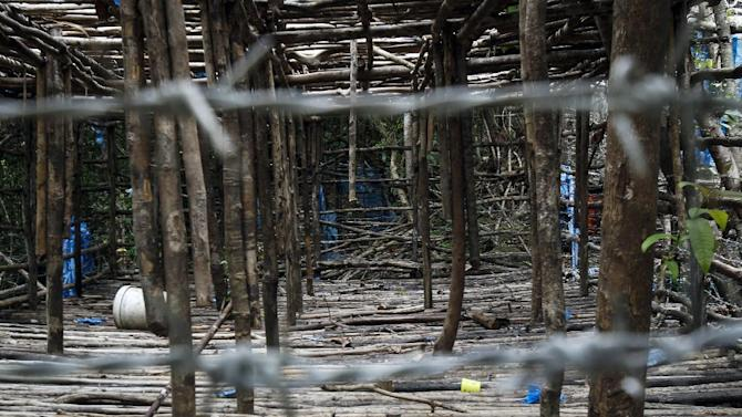 An abandoned cage is photographed at a camp found in Wang Burma at the Malaysia-Thailand border outside Wang Kelian, Malaysia on Tuesday, May 26, 2015. Malaysian forensic teams exhumed a body from a shallow grave at an abandoned camp on Tuesday that was used by human traffickers, the first of what police predicted would be more grim findings as they combed through a cluster of jungle camps on the border with Thailand. (AP Photo/Joshua Paul)