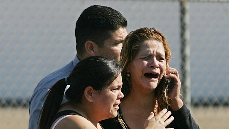 An unidentified woman cries as she's rushed into a car after learning of a workplace shooting  Tuesday, Nov. 6, 2012, in Fresno, Calif.  A parolee who worked at a California chicken processing plant opened fire at the business on Tuesday, killing one person and wounding three others, before shooting himself, police said.   (AP Photo/Gary Kazanjian)