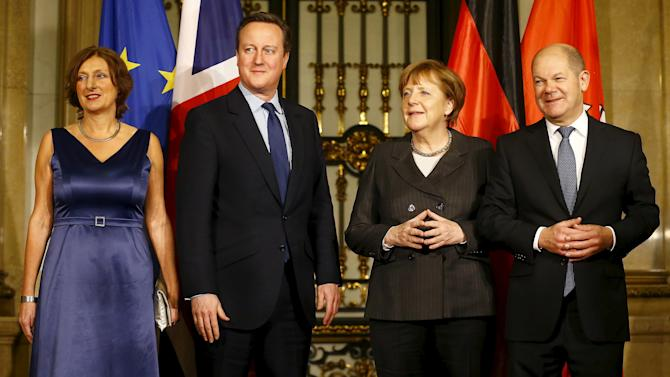 "German Chancellor Merkel and Britain's Prime Minister Cameron pose for photo as they are welcomed by Hamburg's Mayor Scholz and his wife before traditional historic banquet ""Matthiae-Mahlzeit"" (St. Matthew's Day Banquet) at town hall in Hamburg"
