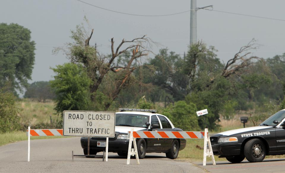 Texas State Troopers sit in front of a closed road due to storm damage in Granbury, Texas, Friday, May 17, 2013. On Wednesday an EF-4 tornado hit the small north Texas town. (AP Photo/Mike Fuentes)