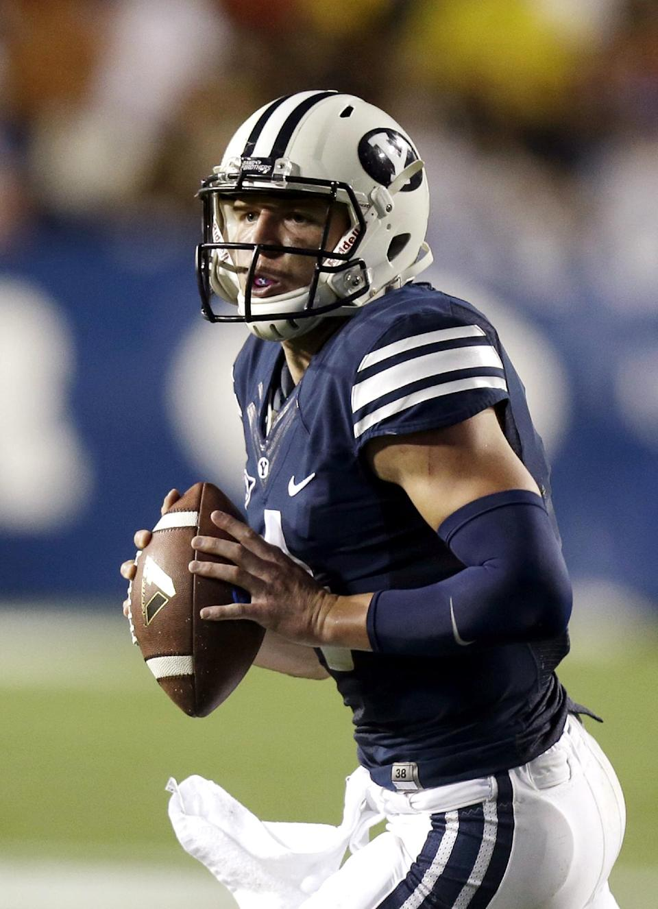 Brigham Young quarterback Taysom Hill (4) carries the ball as he looks down field in the second quarter during an NCAA college football game against Texas, Saturday, Sept. 7, 2013, in Provo, Utah. (AP Photo/Rick Bowmer)