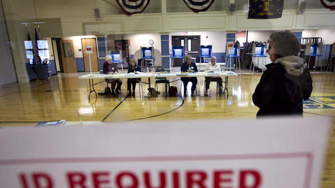 FILE - This April 24, 2012 file photo shows a sign at the entrance of a polling station in East Greenwich, R.I., advises voters that identification is required. President Barack Obama's campaign is recruiting legions of lawyers to handle disputes that may arise from now through Election Day. Thousands of attorneys and support staffers have agreed to aid in the effort, providing legal support that appears to be unrivaled by Republicans or precedent. (AP Photo/Steven Senne, File)