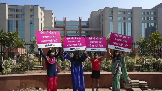 """Women in traditional dresses protest outside the court where the accused in a gang rape of a 23-year-old woman will be tried, in New Delhi, India, Monday, Jan. 21, 2013. Legal proceedings in the fatal gang-rape attack on a student in India's capital were set to begin Monday in a fast-track court for crimes against women that has stirred debate over how best to deliver justice to rape victims. Placards read as, """"No dress is an invitation to rape."""" (AP Photo/Saurabh Das)"""