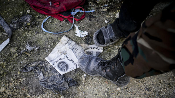 A Free Syrian Army fighter steps on a paper with the photo of Syrian President Bashar Assad in Aleppo, Syria, Tuesday, Jan. 15, 2013. Two explosions struck the main university in the northern Syrian city of Aleppo on Tuesday, causing an unknown number of casualties, state media and anti-government activists said. (AP Photo/Andoni Lubaki)