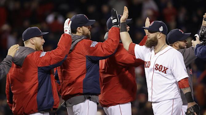Boston Red Sox's Mike Napoli, right, celebrates with John Lackey, center, and teammates after Game 1 of baseball's World Series against the St. Louis Cardinals Wednesday, Oct. 23, 2013, in Boston. The Red Sox won 8-1 to take a 1-0 lead in the series