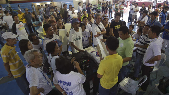 Election workers explain to voters a procedure after one of the automated machines known as PCOS malfunctioned at a covered court used as a voting center during mid-term elections at a Manila suburb, Philippines on Monday May 13, 2013. The country is electing local officials from senators to congressmen and down to municipal mayors during today's mid-term elections. (AP Photo/Aaron Favila)