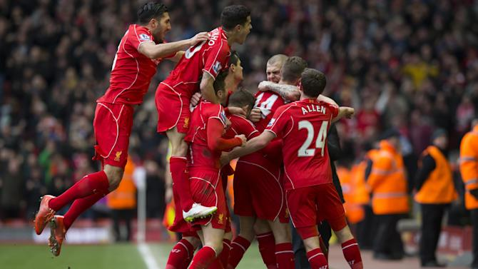 Liverpool's Jordan Henderson, second right with back to camera, celebrates with jubilant teammates after scoring during the English Premier League soccer match between Liverpool and Manchester City at Anfield Stadium, Liverpool, England, Sunday, March 1, 2015. (AP Photo/Jon Super)