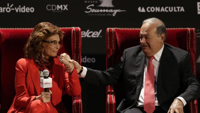 Mexican tycoon Slim holds the hand of Italian actress Loren during a news conference at the Soumaya museum in Mexico City