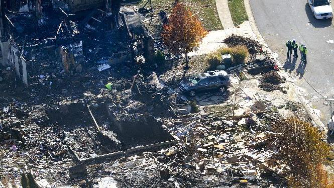 Citizens Energy workers continue their investigation Monday afternoon Nov. 12, 2012 by digging into the front sidewalk looking for possible explanation into the explosion in Indianapolis.   They are checking gas line, but caution it is too soon to rule other possible causes,    (AP Photo/ WTHR Chopper 13 /The Indianapolis Star, Matt Kryger)  NO SALES