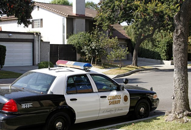 An unoccupied Los Angeles County Sheriff&#39;s Department patrol car is parked across from the home, background, of Nakoula Basseley Nakoula, the man who made the film &quot;Innocence of Muslims&quot; that has sparked violent protests, in Cerritos, Calif., Tuesday, Sept. 25, 2012. The filmmaker has received death threats and was forced into hiding, putting his home up for sale, after the 14-minute movie trailer rose to prominence. (AP Photo/Reed Saxon)