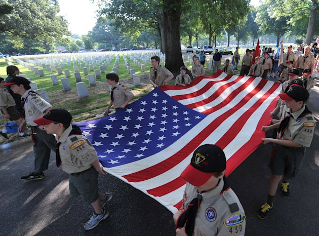 Members of Boy Scout Troop 450 and 278 lead the parade carrying a large American flag during the Memorial Day observance ceremony at the Memphis National Cemetery in Memphis, Tenn. Saturday, May 26, 2012. For 29 years members of the Boy Scouts, Girl Scouts and American Heritage Girls have placed flags on the 42,000 graves at the Memphis National Cemetery during a ceremony honoring veterans for the Memorial Day Celebration. (AP Photo/The Commercial Appeal, Chris Desmond)