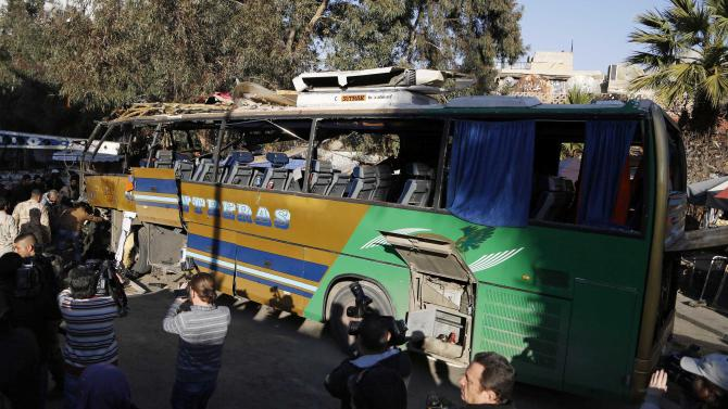 Members of Syrian security services and journalists look at the wreckage of a bus on which an explosion occurred, in central Damascus
