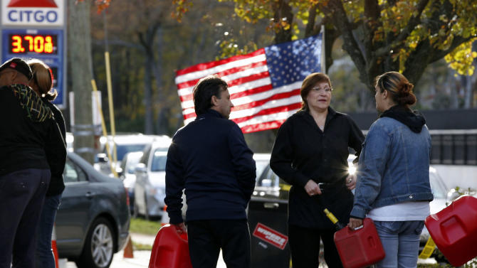 FILE - In this Saturday, Nov. 3, 2012, file photo, people wait in line with containers to purchase gasoline at filling station in Metuchen, N.J. The price of oil is slightly higher Monday, Nov. 5, 2012, as investors remain cautious ahead of the U.S. presidential election. They're also assessing how much demand for oil has dropped in the storm-stricken Northeast. (AP Photo/Mel Evans, File)