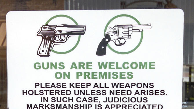 "A sign on the front door of Shooters Grill in Rifle, Colo., June 23, 2014, welcomes sidearms. A western Colorado restaurant doesn't just allow open gun carrying. Its waitresses carry loaded weapons right on their hips. At Shooters Grill in Rifle, open display of firearms is encouraged. A sign on the front door reads, ""Guns are welcome on premises. Please keep all weapons holstered, unless the need arises. In such cases, judicious marksmanship is appreciated."" The restaurant also hosts concealed carry training that qualifies customers for Colorado and Utah permits. The $75 price tag includes dinner. (AP Photo/Glenwood Springs Post Independent, Christopher Mullen)"