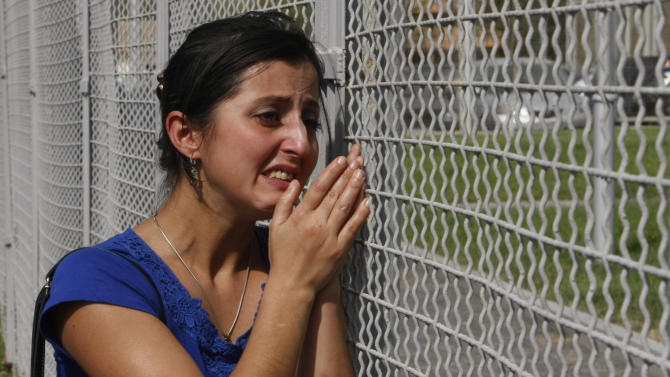 A woman cries at a prison fence as she and fellow protesters demand to see their family members during a protest rally against prison abuse in Tbilisi, Georgia, Thursday, Sept. 20, 2012. Street protests against the brutal abuse of prisoners escalated Thursday in the Georgian capital, fueling anger against the Western-allied government and possibly boosting support for the opposition before a tight parliamentary election. Two days after television stations aired videos of guards beating inmates and raping them with truncheons and brooms, thousands rallied outside the Interior Ministry and the Tbilisi prison where the abuse occurred. The protesters, some carrying brooms, then marched down the capital's main avenue to the presidential palace to demand the ouster of the interior minister. (AP Photo / Shakh Aivazov)