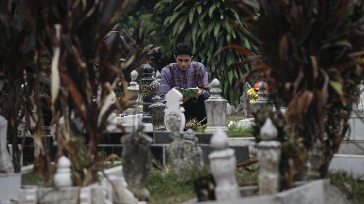A Muslim man offers prayers at his relatives' grave yard during the first day of the Eid al-Fitr, marking the end of the holy fasting month of Ramadan in Kuala Lumpur, Malaysia, Monday, July. 28, 2014. The Eid al-Fitr, one of the holiest religious practices, is celebrated with prayers and family reunions and other festivities among Muslims all over the world. (AP Photo)