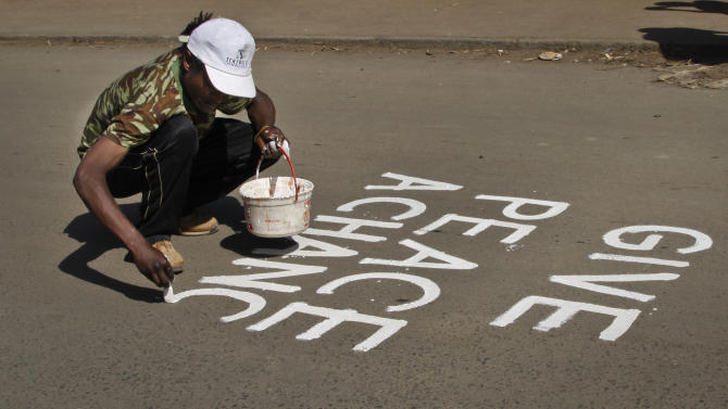 A graffiti artist paints a peace slogan on a road in the Kibera slum of Nairobi, Kenya Saturday, March 9, 2013. Uhuru Kenyatta - the son of Kenya's founding father and a man accused by an international court of helping orchestrate the vicious violence that marred the nation's last vote - was certified as the winner on Saturday of Kenya's presidential election by the slimmest majority - 50.07 percent. (AP Photo/Khalil Senosi)