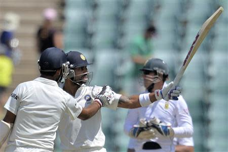 India's Kohli is congratulated by Pujara during the first day of their cricket test match against South Africa in Johannesburg