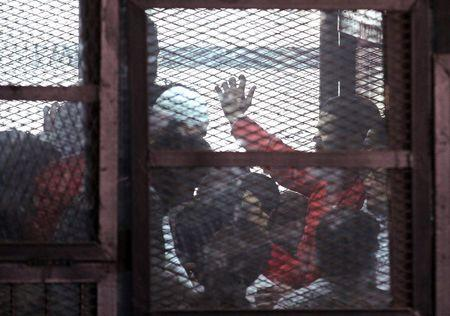 The accused are seen in a cage during a trial of 200 charged with belonging to the Ansar Bait al-Maqdis group, in Cairo court